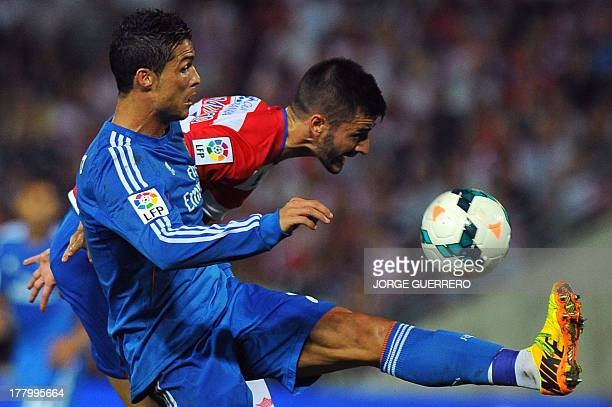 Real Madrid's Portuguese forward Cristiano Ronaldo vies with Granada's midfielder Fran Rico during the Spanish league football match Granada FC vs...