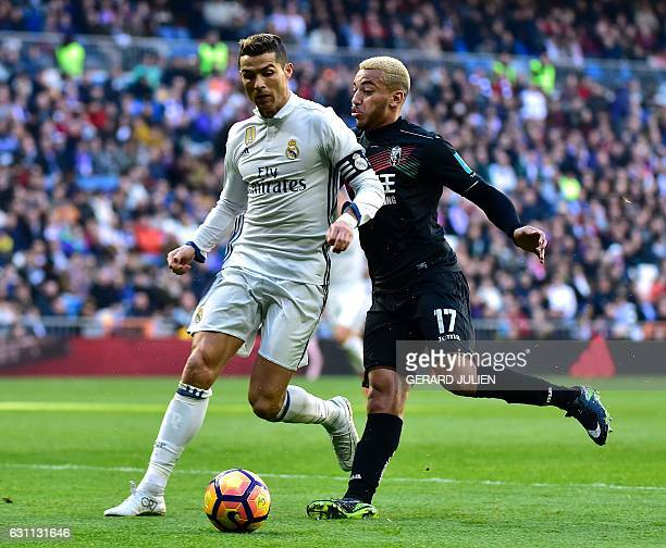 Real Madrid's Portuguese forward Cristiano Ronaldo vies with Granada's Portuguese defender Ruben Vezo during the Spanish league football match Real...