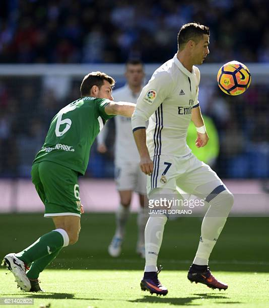 Real Madrid's Portuguese forward Cristiano Ronaldo vies with Leganes's midfielder Alberto Martin during the Spanish league football match Real Madrid...