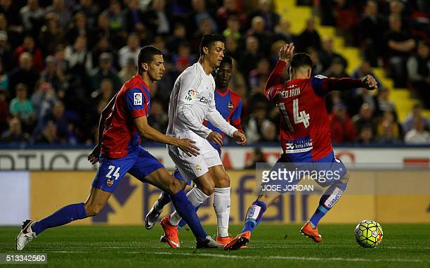 Real Madrid's Portuguese forward Cristiano Ronaldo vies with Levante's Moroccan defender Zou Feddal during the Spanish league football match Levante...