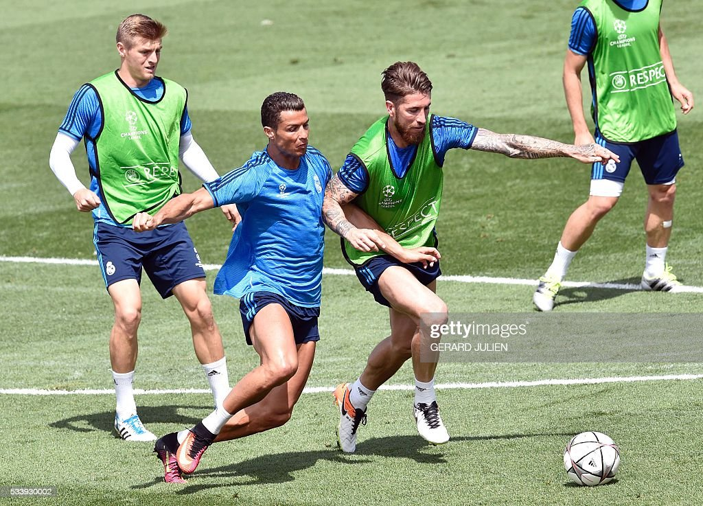 Real Madrid's Portuguese forward Cristiano Ronaldo (C) vies with Real Madrid's defender Sergio Ramos (R) next to Real Madrid's German midfielder Toni Kroos (L) during a training session on the club's Open Media Day at Real Madrid sport city in Madrid on May 24, 2016. / AFP / GERARD