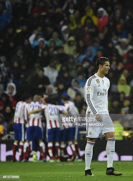 Real Madrid's Portuguese forward Cristiano Ronaldo walks as Atletico Madrid's players celebrate the second goal of forward Fernando Torres during the...