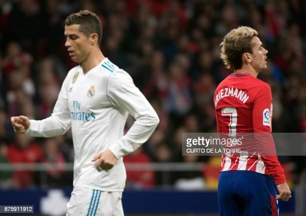 Real Madrid's Portuguese forward Cristiano Ronaldo walks past Atletico Madrid's French forward Antoine Griezmann during the Spanish league football...