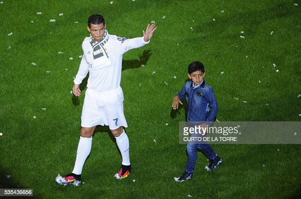 Real Madrid's Portuguese forward Cristiano Ronaldo waves as he walks with his son during celebrations for their 11th UEFA Champions Cup at the...