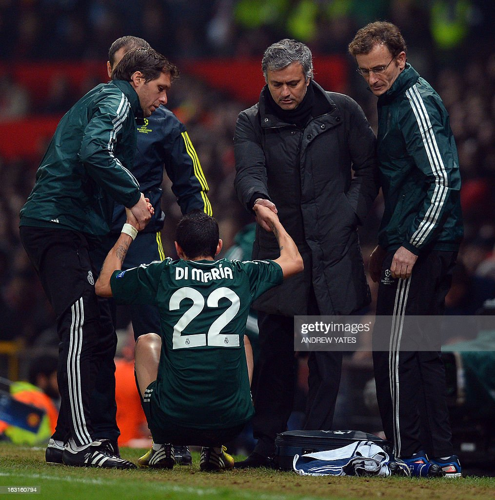 Real Madrid's Portuguese manager Jose Mourinho (2R) helps Real Madrid's Argentinian midfielder Angel di Maria to his feet after an injury Real Madrid's Portuguese manager Jose Mourinho leaves the field at half time during the UEFA Champions League round of 16 second leg football match between Manchester United and Real Madrid at Old Trafford in Manchester, northwest England on March 5, 2013.