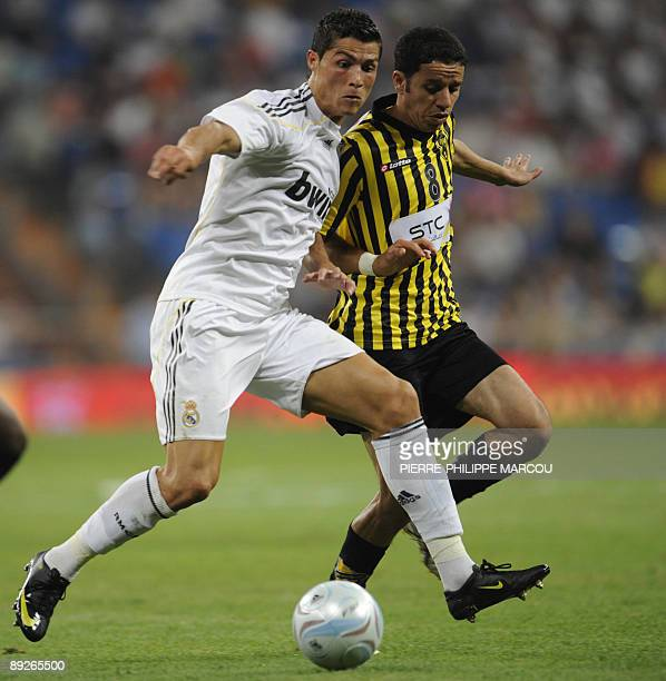 Real Madrid's Portuguese midfielder Cristiano Ronaldo vies with AlIttihad's Manaf Aboshgair during their Peace Cup football match at Santiago...