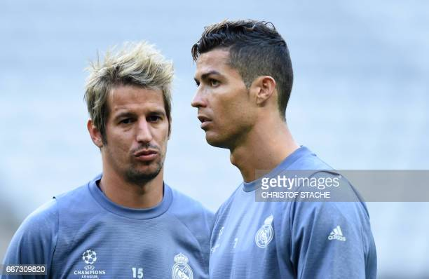 Real Madrid's Portuguese striker Cristiano Ronaldo and his compatriot Portuguese Fabio Coentrao speak together during a training session on the eve...