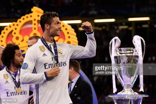 Real Madrid's Portuguese striker Cristiano Ronaldo celebrates next to the trophy after Real Madrid won the UEFA Champions League final football match...