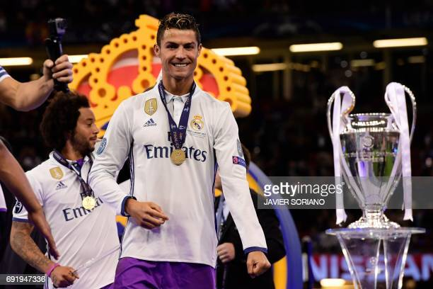 TOPSHOT Real Madrid's Portuguese striker Cristiano Ronaldo celebrates next to the trophy after Real Madrid won the UEFA Champions League final...