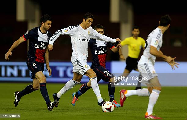 Real Madrid's Portuguese striker Cristiano Ronaldo dribbles past Paris SaintGermain's Italian midfielders Thiago Motta and Marco Verratti during...