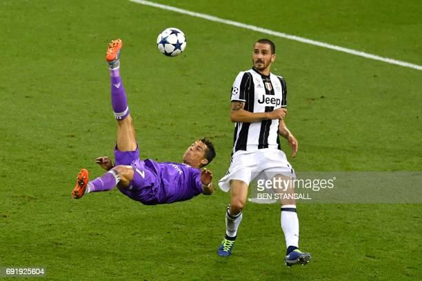 TOPSHOT Real Madrid's Portuguese striker Cristiano Ronaldo kicks a scissor kick ahead of Juventus' Italian defender Leonardo Bonucci during the UEFA...