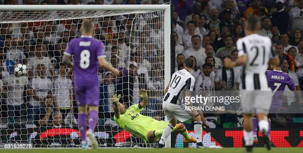 Real Madrid's Portuguese striker Cristiano Ronaldo shoots and scores their third goal past Juventus' Italian goalkeeper Gianluigi Buffon during the...