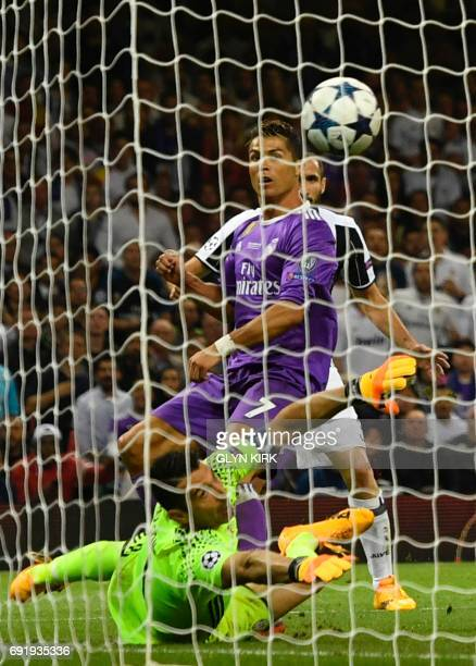 Real Madrid's Portuguese striker Cristiano Ronaldo shoots over Juventus' Italian goalkeeper Gianluigi Buffon to score their third goal during the...