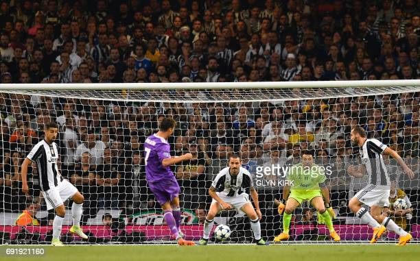 Real Madrid's Portuguese striker Cristiano Ronaldo shoots to score the opening goal of the UEFA Champions League final football match between...