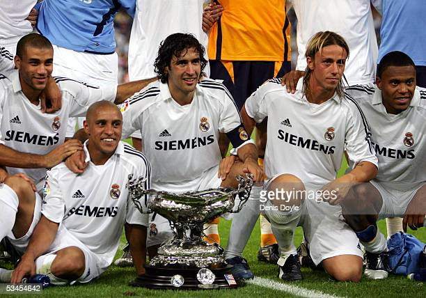 Real Madrid's Roberto Carlos Raul Gonzalez Jose Maria Gutierrez Hernandez and Julio Baptista pose with the Santiago Bernabeu trophy after beating a...