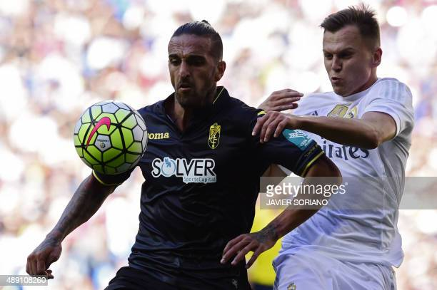 Real Madrid's Russian midfielder Denis Cheryshev vies with Granada's Portuguese defender Miguel Lopes during the Spanish league football match Real...
