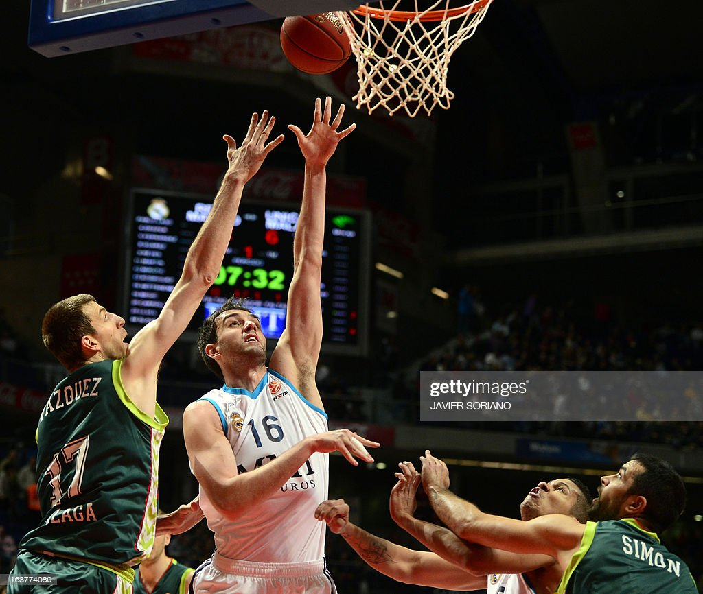 Real Madrid's Slovenian centre Mirza Begic (2ndL) shoots in front of Unicaja's centre Fran Vazquez (L) and Unicaja's Croatian forward Krunoslav Simon (R) during the Euroleague basketball match Real Madrid vs Unicaja Malaga at the Palacio de los Deportes in Madrid on March 15, 2013.