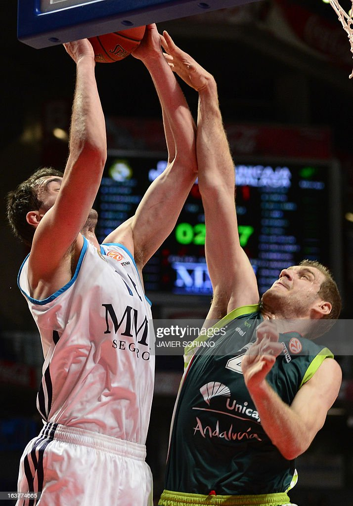 Real Madrid's Slovenian centre Mirza Begic (L) vies with Unicaja's Croatian centre Luka Zoric during the Euroleague basketball match Real Madrid vs Unicaja at the Palacio de los Deportes in Madrid on March 15, 2013.