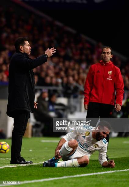 Real Madrid's Spanish defender Dani Carvajal groans beside Atletico Madrid's Argentinian coach Diego Simeone during the Spanish league football match...