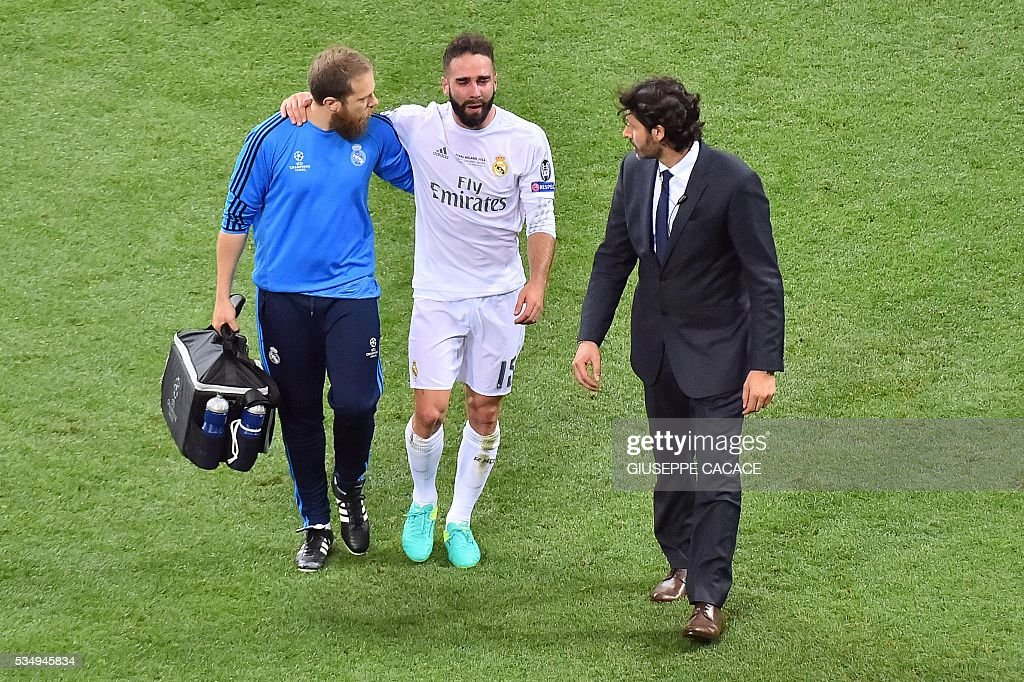 Real Madrid's Spanish defender Dani Carvajal is escorted off the pitch during the UEFA Champions League final football match between Real Madrid and Atletico Madrid at San Siro Stadium in Milan, on May 28, 2016. / AFP / GIUSEPPE