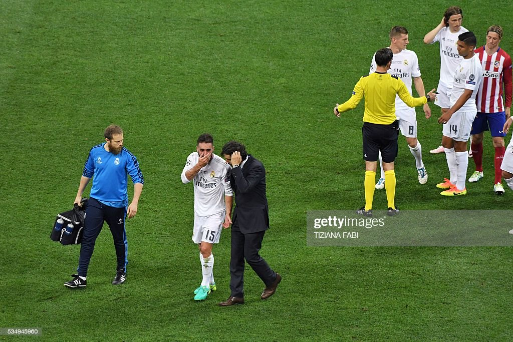 Real Madrid's Spanish defender Dani Carvajal is escorted off the pitch during the UEFA Champions League final football match between Real Madrid and Atletico Madrid at San Siro Stadium in Milan, on May 28, 2016. / AFP / TIZIANA