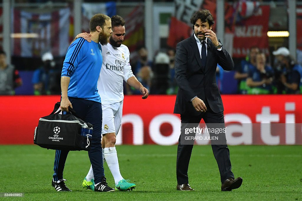 Real Madrid's Spanish defender Dani Carvajal (C) leaves the pitch after sustaining an injury during the UEFA Champions League final football match between Real Madrid and Atletico Madrid at San Siro Stadium in Milan, on May 28, 2016. / AFP / GERARD