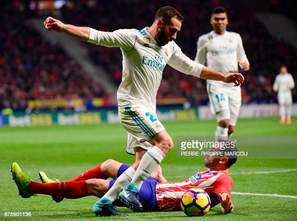 Real Madrid's Spanish defender Dani Carvajal vies with Atletico Madrid's Uruguayan defender Diego Godin during the Spanish league football match...