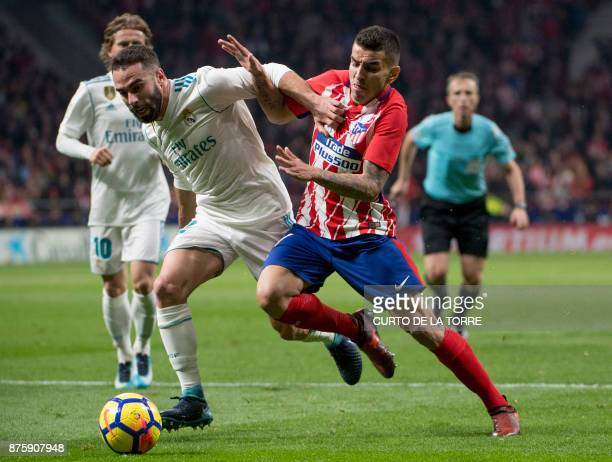 Real Madrid's Spanish defender Dani Carvajal vies with Atletico Madrid's Argentinian forward Angel Correa during the Spanish league football match...