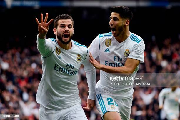 Real Madrid's Spanish defender Nacho Fernandez celebrates with Real Madrid's Spanish midfielder Marco Asensio after scoring a goal during the Spanish...