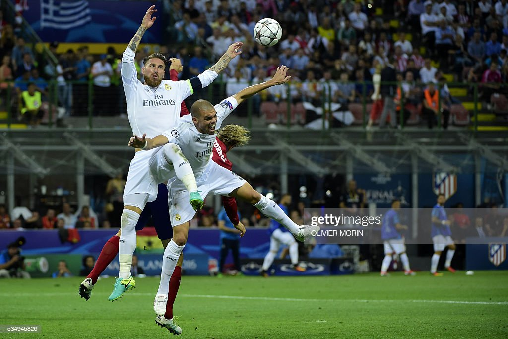 Real Madrid's Spanish defender Sergio Ramos (L) and Real Madrid's Portuguese defender Pepe (C) jump for the ball with Atletico Madrid's Spanish forward Fernando Torres during the UEFA Champions League final football match between Real Madrid and Atletico Madrid at San Siro Stadium in Milan, on May 28, 2016. / AFP / OLIVIER
