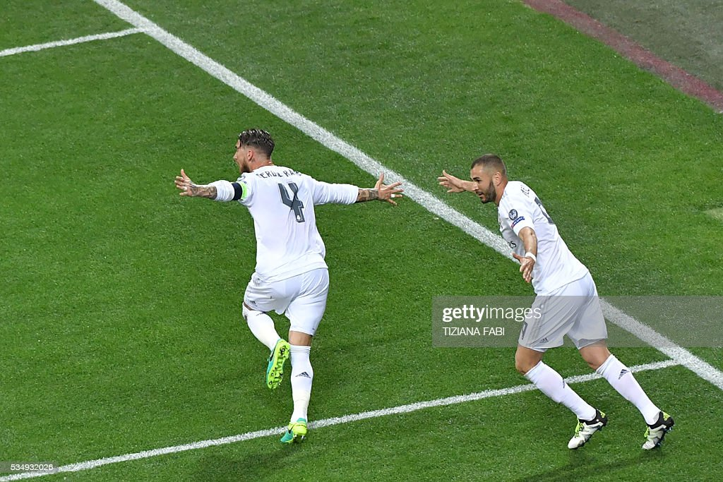 Real Madrid's Spanish defender Sergio Ramos (4) and team mate French forward Karim Benzema react after Ramos scored the first goal of the match during the UEFA Champions League final football match between Real Madrid and Atletico Madrid at San Siro Stadium in Milan, on May 28, 2016. / AFP / TIZIANA
