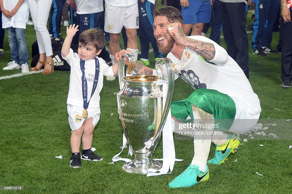Real Madrid's Spanish defender Sergio Ramos flanked by his son poses with the trophy after Real Madrid won the UEFA Champions League final football match between Real Madrid and Atletico Madrid at San Siro Stadium in Milan, on May 28, 2016. / AFP / Filippo MONTEFORTE
