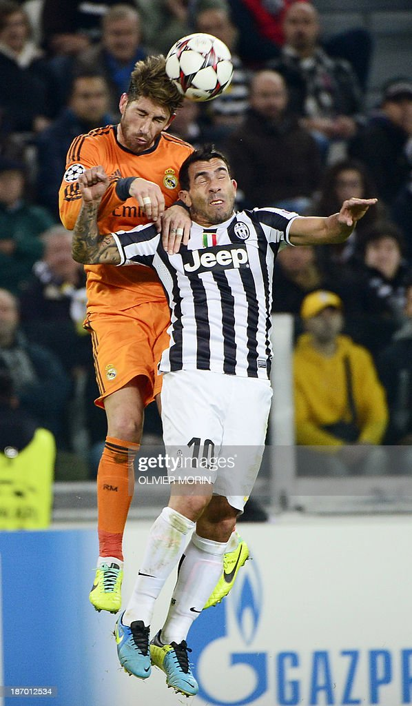 Real Madrid's Spanish defender Sergio Ramos (L) jumps for the ball with Juventus' Argentinian foward Carlos Tevez (R) during the UEFA Champions League Group B football match Juventus vs Real Madrid at the Juventus stadium in Turin on November 5, 2013.
