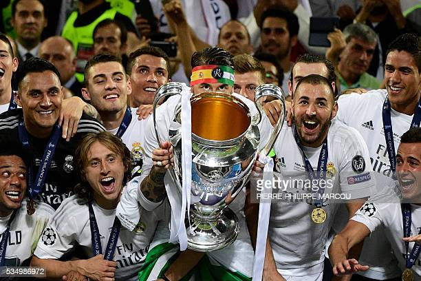 Real Madrid's Spanish defender Sergio Ramos lifts the trophy next to Real Madrid's Croatian midfielder Luka Modric and Real Madrid's French forward...
