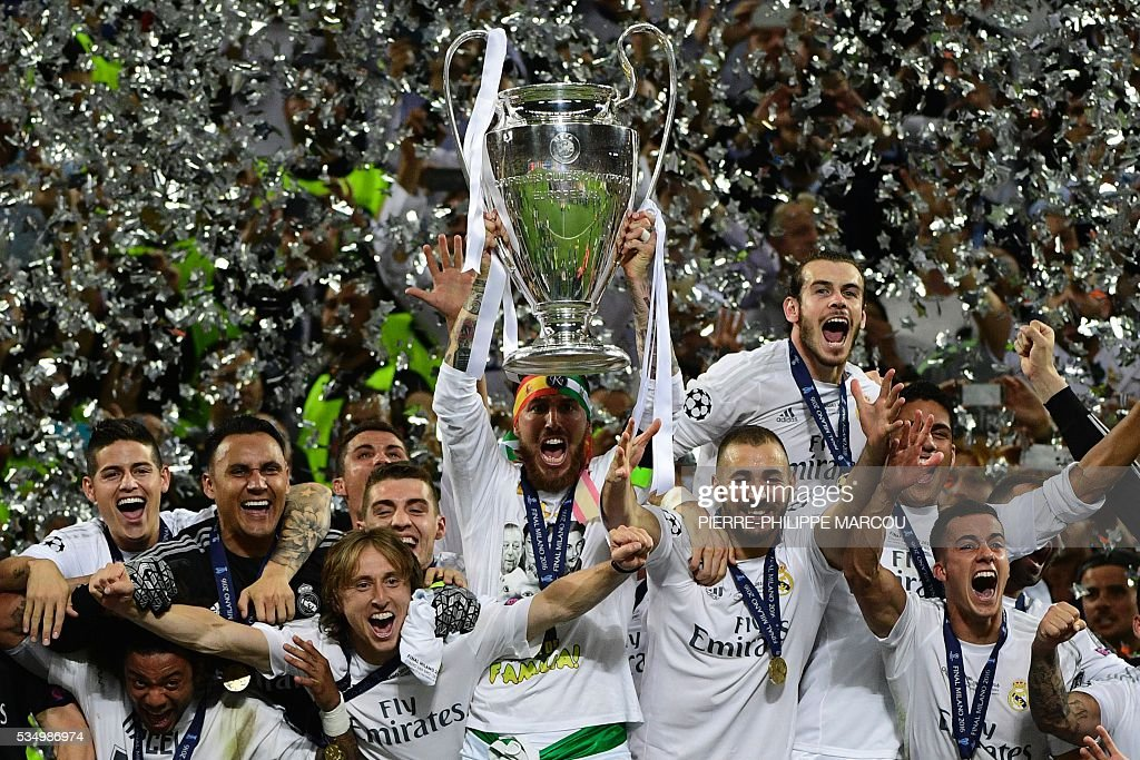 Real Madrid's Spanish defender Sergio Ramos (C) lifts the trophy next to Real Madrid's Croatian midfielder Luka Modric (C-L) and Real Madrid's French forward Karim Benzema (C-R) after Real Madrid won the UEFA Champions League final football match between Real Madrid and Atletico Madrid at San Siro Stadium in Milan, on May 28, 2016. / AFP / PIERRE