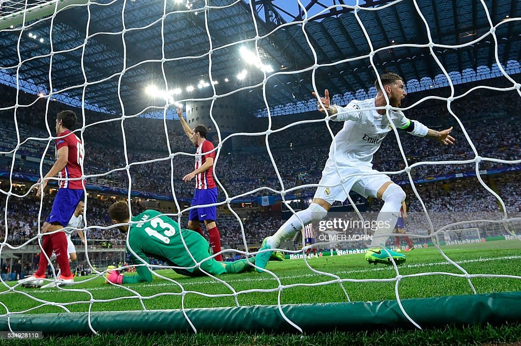 Real Madrid's Spanish defender Sergio Ramos (R) reacts after scoring the opening goal during the UEFA Champions League final football match between Real Madrid and Atletico Madrid at San Siro Stadium in Milan, on May 28, 2016. / AFP / OLIVIER