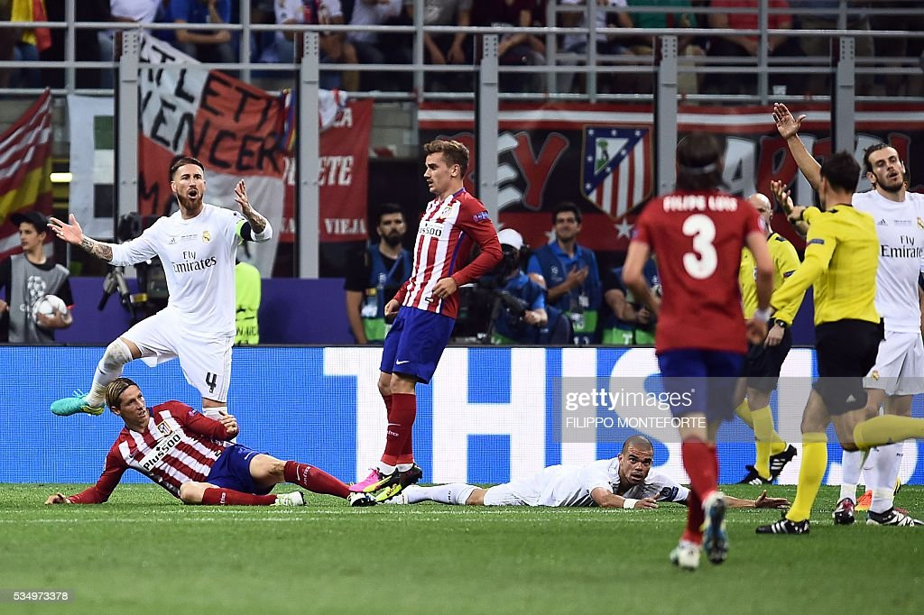 Real Madrid's Spanish defender Sergio Ramos (up L) reacts next to Atletico Madrid's French forward Antoine Griezmann (C) as Atletico Madrid's Spanish forward Fernando Torres (L) and Real Madrid's Portuguese defender Pepe (R) lie on the ground during the UEFA Champions League final football match between Real Madrid and Atletico Madrid at San Siro Stadium in Milan, on May 28, 2016. / AFP / FILIPPO