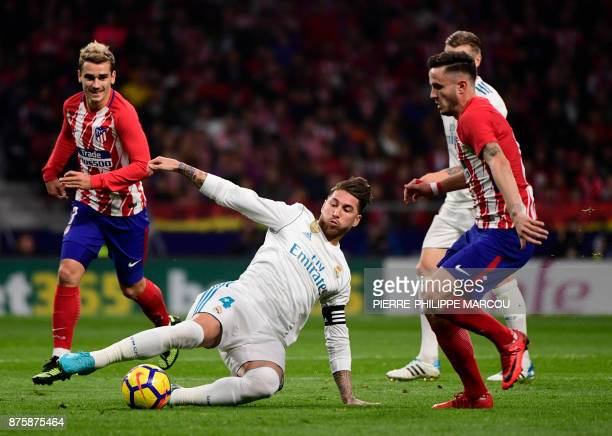 Real Madrid's Spanish defender Sergio Ramos vies with Atletico Madrid's French forward Antoine Griezmann and Atletico Madrid's Spanish midfielder...
