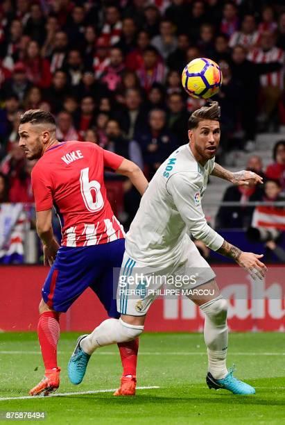 Real Madrid's Spanish defender Sergio Ramos vies with Atletico Madrid's Spanish midfielder Koke during the Spanish league football match Atletico...