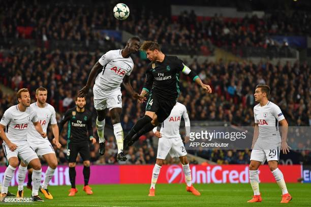 Real Madrid's Spanish defender Sergio Ramos wins a header as Tottenham Hotspur's Colombian defender Davinson Sanchez defends during the UEFA...