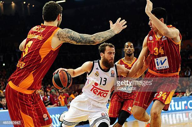 Real Madrid's Spanish forward Sergio Rodriguez challenges Galatasaray's Serbian forward Vladimir Micov US guard Justin Carter and Turkish forward Ege...