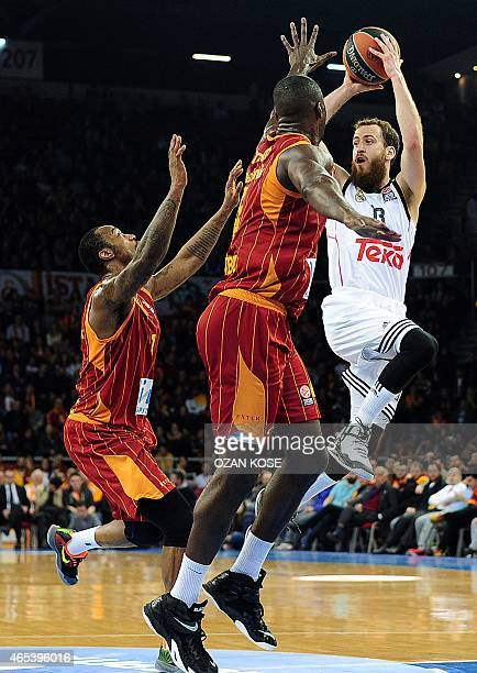 Real Madrid's Spanish guard Sergio Rodriguez challenges Galatasaray's US centre Patric Young and US guard Justin Carter during the Euroleague top 16...