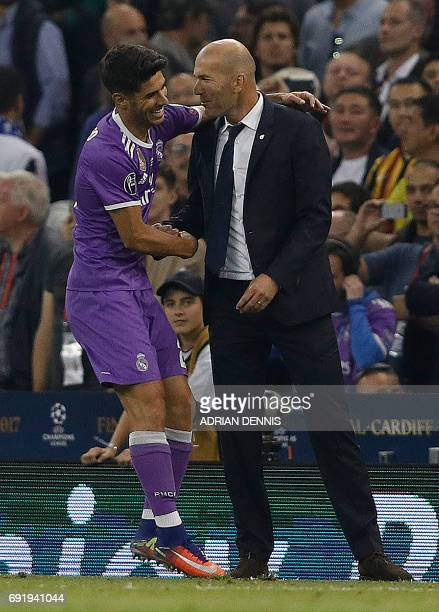 Real Madrid's Spanish midfielder Marco Asensio celebrates with Real Madrid's French coach Zinedine Zidane after scoring their fourth goal during the...