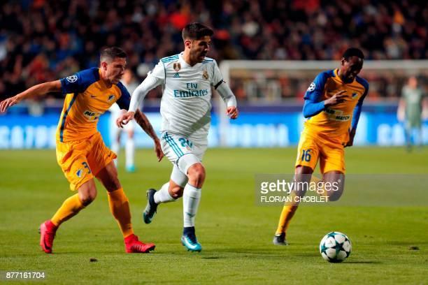 Real Madrid's Spanish midfielder Marco Asensio vies for the ball with Apoel's Spanish defender Roberto Lago and Apoel's Brazilian midfielder Vinicius...