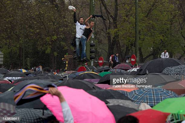 Real Madrid's supporters wait under the rain for their team to celebrate at Cibeles Square on May 3 in Madrid Spain Real Madrid are celebrating...