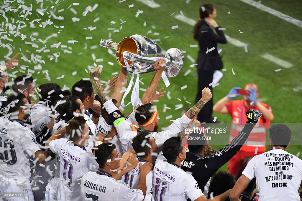 Real Madrid's team players celebrate with the trophy after winning the UEFA Champions League final football match against Atletico Madrid at the San Siro Stadium in Milan on May 28, 2016. Real Madrid beat city rivals Atletico for the second time in three years to win the Champions League for the 11th time. / AFP / TIZIANA