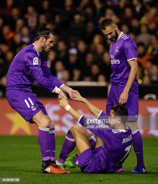 Real Madrid's Welsh forward Gareth Bale and Real Madrid's French forward Karim Benzema helpup Real Madrid's Portuguese forward Cristiano Ronaldo...