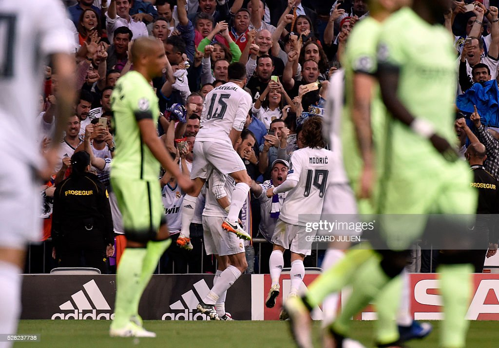 Real Madrid's Welsh forward Gareth Bale (C bottom) celebrates a goal with Real Madrid's defender Dani Carvajal (C top) during the UEFA Champions League semi-final second leg football match Real Madrid CF vs Manchester City FC at the Santiago Bernabeu stadium in Madrid, on May 4, 2016. / AFP / GERARD
