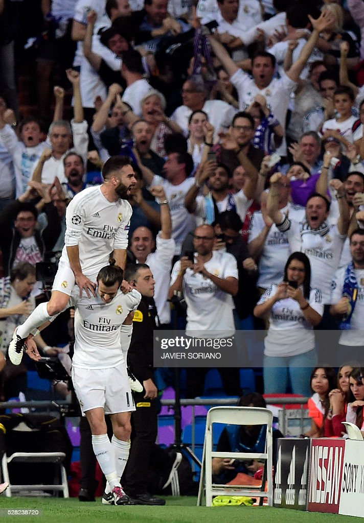 Real Madrid's Welsh forward Gareth Bale (bottom) celebrates a goal with teammate Real Madrid's defender Dani Carvajal during the UEFA Champions League semi-final second leg football match Real Madrid CF vs Manchester City FC at the Santiago Bernabeu stadium in Madrid, on May 4, 2016. / AFP / JAVIER