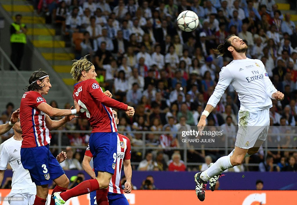Real Madrid's Welsh forward Gareth Bale (R) heads the ball past Atletico Madrid's Brazilian defender Filipe Luis (L) and Atletico Madrid's Spanish forward Fernando Torres (C) during the UEFA Champions League final football match between Real Madrid and Atletico Madrid at San Siro Stadium in Milan, on May 28, 2016. / AFP / GERARD